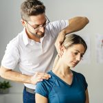Physical therapist working with patient on neck pain
